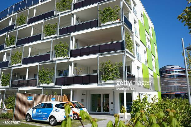 Ecological sustainable green building electric cars in front