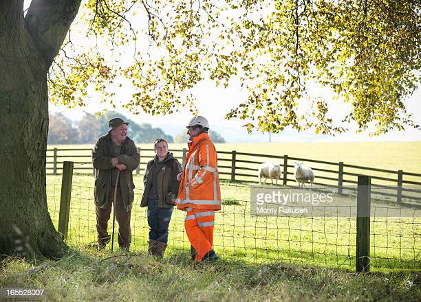 Ecologist talking to local farmer and son near site of surface coal mine