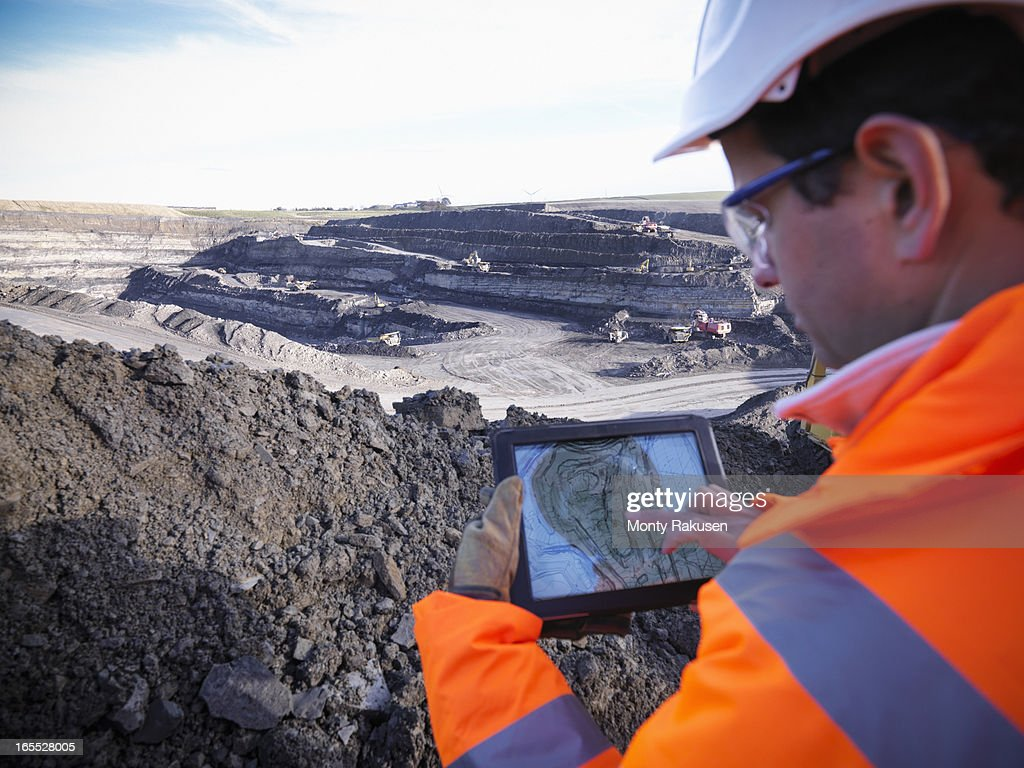 Ecologist using digital tablet surveying surface coal mine site, elevated view : Stock Photo