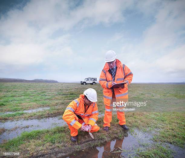 ecologists at surface coal mine restoration inspecting pond - ecologist stock pictures, royalty-free photos & images