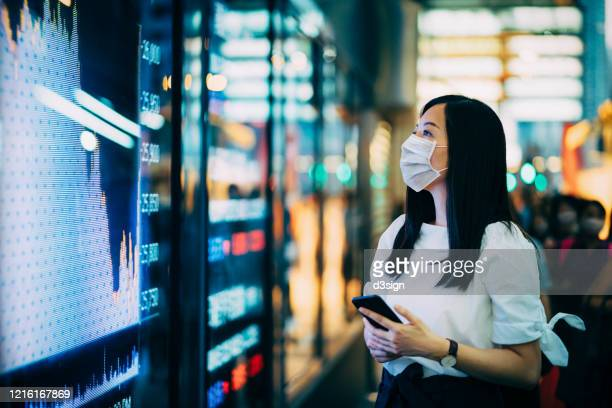 economic and financial impact during the covid-19 health crisis deepens. businesswoman with protective face mask checking financial trading data on smartphone by the stock exchange market display screen board in downtown financial district showing stock m - covid-19 ストックフォトと画像