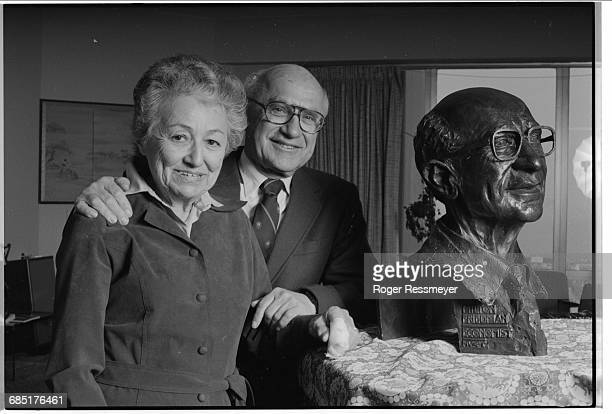 Economist and author Milton Friedman with his wife and co-author Rose near a sculpture bust.