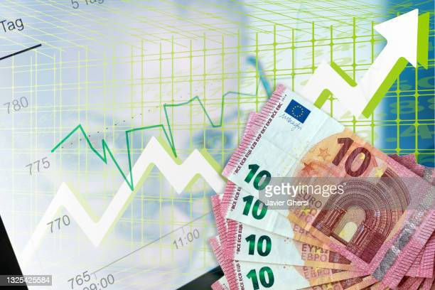 economy graph: euros in cash and rising arrow. - economist stock pictures, royalty-free photos & images