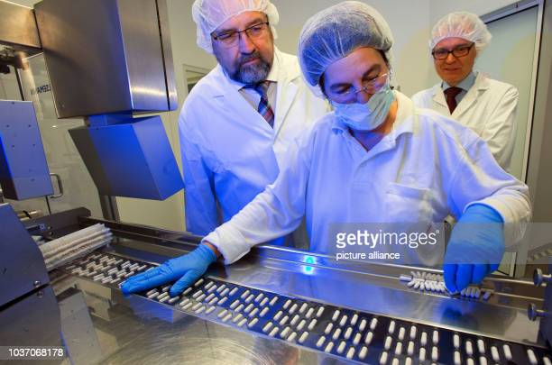 Economy Minister of MecklenburgWestern Pomerania Harry Glawe speaks with Marlies Fuhrmann at the packaging line of new lozenges in the laboratory of...