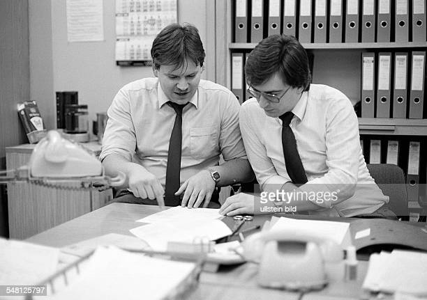 economy work occupation two office clerks at the writing desk in a talk telephones file cabinet aged 25 to 35 years Uwe Wolfgang