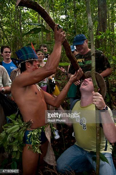 Ecotourism in Amazon rain forest Tukano indian teaches tourists how to get water from the cipó d'água a kind of liana also known as 'cipó vermelho'...
