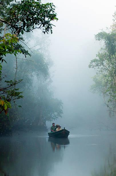 Eco-tourists enjoying boatride on Menanggol tribituary of Sungai Kinabatasngan in early morning mist, near Sukau.