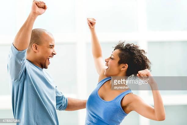 Célébrant explosion de couple afro-américain avec les bras levés.