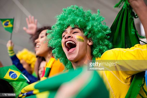 ecstatic brazilian fan watching a football game - world cup stock photos and pictures