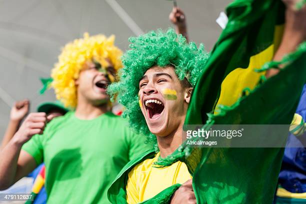 ecstatic brazilian fan watching a football game - fan enthusiast stock photos and pictures