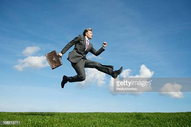 Ecstatic Businessman Jumping Outdoors in Blue Sky Green Field