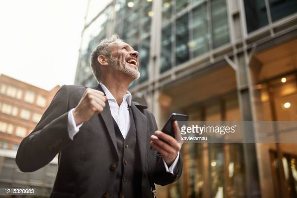 ecstatic businessman learning good news on smart phone - looking stock pictures, royalty-free photos & images