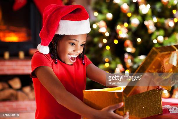 Ecstatic girl opening Christmas presents.