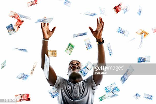 ecstatic man catching raining banknotes - south african currency stock photos and pictures