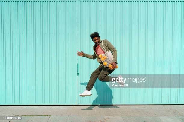 ecstatic man dancing in front of turquoise wall during sunny day - männer über 30 stock-fotos und bilder