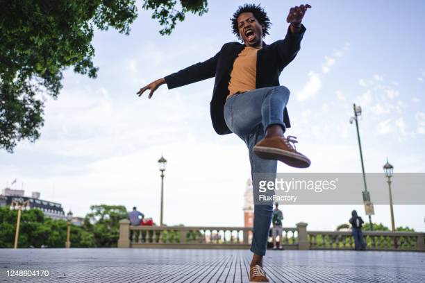 ecstatic man dancing on a plaza in buenos aires - standing on one leg stock pictures, royalty-free photos & images