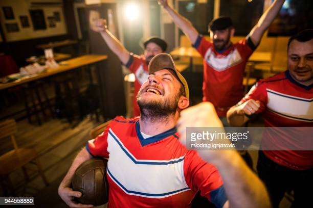 ecstatic men watching soocer game in a bar - match sport stock pictures, royalty-free photos & images