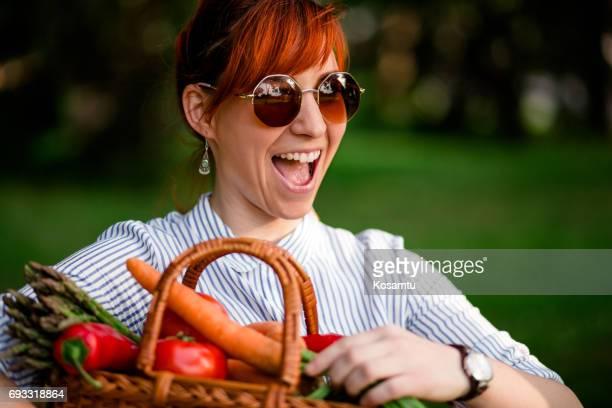 Extatique femme rousse portant panier plein de légumes