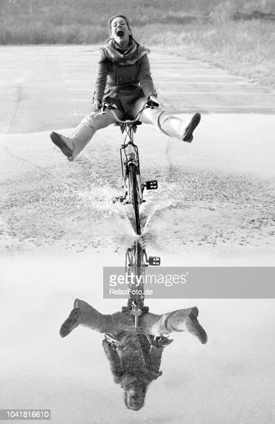 Ekstatische schreien Mitte Erwachsene Frau Radfahren durch Pfütze mit Reflexion