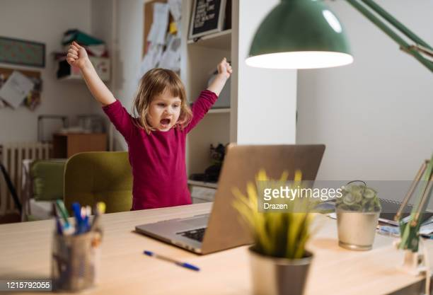 ecstatic three year old girl celebrating winning on video game on laptop - winning stock pictures, royalty-free photos & images