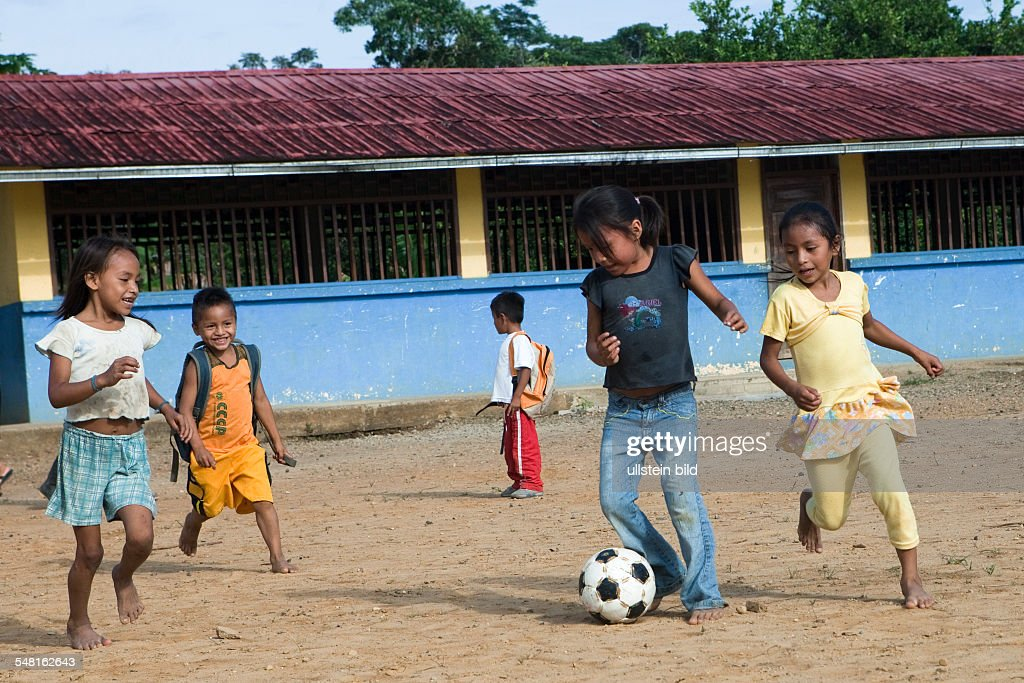 Ecuador Curaray - A village without any road connection in the rainforest of the Oriente, 150 km east of Puyo. Kids playing soccer in the schoolyard before lessons start : News Photo