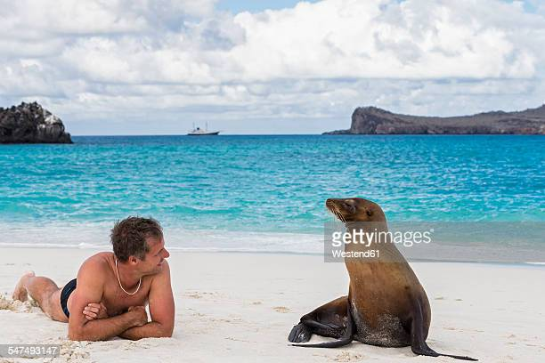 Ecuador, Galapagos Islands, Espanola, tourist and Galapagos sea lion on beach
