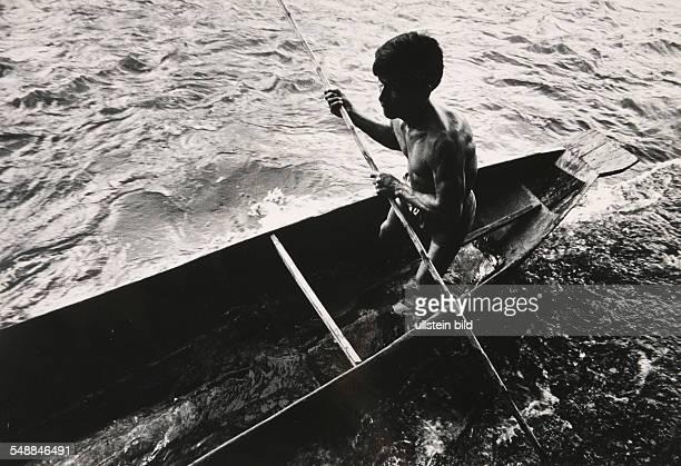 Ecuador Jivaro Indian skillfully navigates his way through the treacherous rapids of the Rio Upano in a dugout canoe