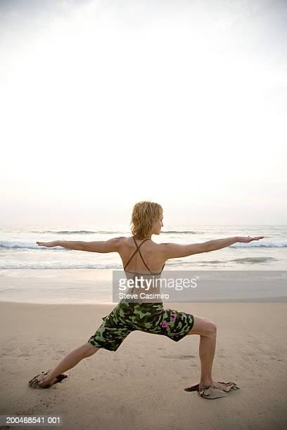 Ecuador, young woman practicing yoga on beach, rear view