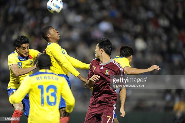 Ecuadorean defender Frickson Erazo heads the ball near teammates Norberto Araujo and Neicer Reasco and Venezuelan forward Nicolas Fedor during a 2011...