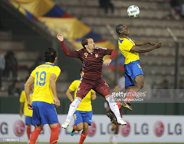 Ecuadorean defender Norberto Araujo looks on as Venezuelan forward Giancarlo Maldonado vies for the ball with Ecuadorean defender Walter Ayovi during...