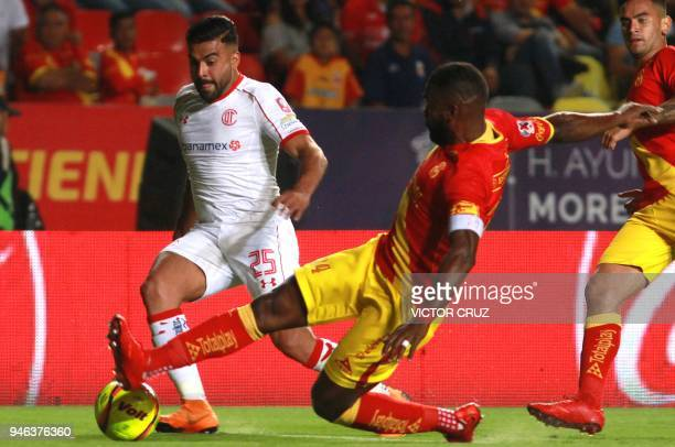 Ecuadorean Gabriel Achilier of Morelia is marked by Argentine Pedro Alexis Canelo of Toluca during their Mexican Clausura football tournament match...