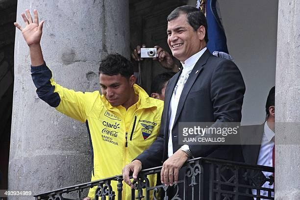 Ecuadorean President Rafael Correa smiles next to Ecuador's national football team player Edison Montero after giving the national flag to captain...
