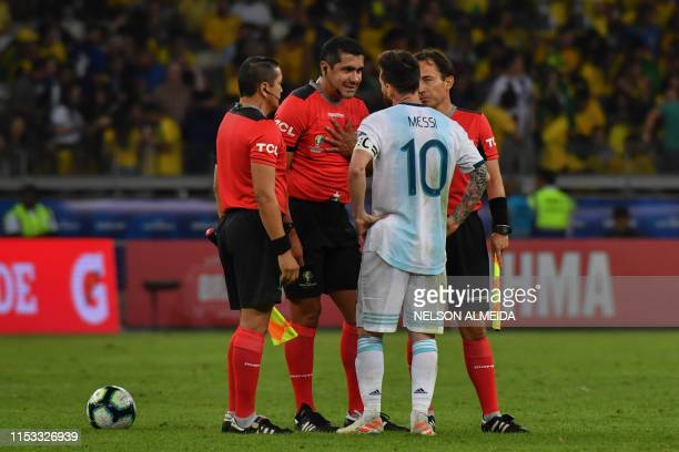 Ecuadorean referee Roddy Zambrano talks to Argentina's Lionel Messi during half-time of the Copa America football tournament semi-final match between...
