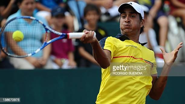 Ecuadorean tennis player Julio Camposano returns the ball to Colombia's Robert Farah during their Davis Cup match in Salinas Ecuador on February 10...