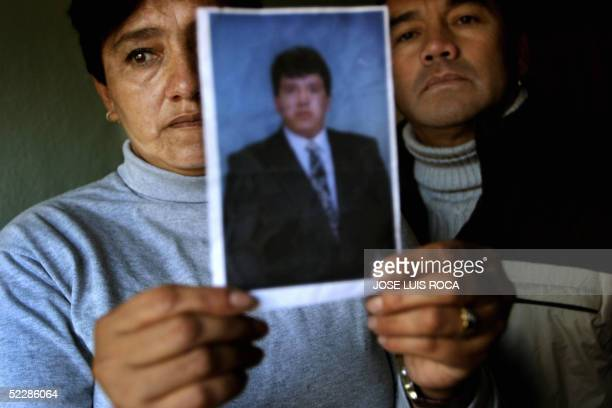 CALOTTI Ecuadorians Teresa and Luis Cisneros show a photograph of their brother Osvaldo 04 March 2005 in Madrid one of the 191 people killed in the...