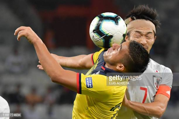 Ecuador's Andres Chicaiza and Japan's Gaku Shibasaki vie for the ball during their Copa America football tournament group match at the Mineirao...