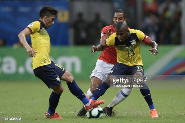 Ecuador's Angel Mena and Enner Valencia vie for the ball with Chile's Jean Beausejour during their Copa America football tournament group match at...