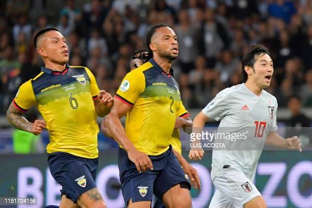 Ecuador's Cristian Ramirez and Arturo Mina and Japan's Shoya Nakajima run during their Copa America football tournament group match at the Mineirao...