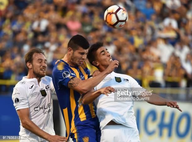 Ecuador's Deportivo Cuenca players Brian Cucco and Matias Contreras vie for the ball with Ruben Monges of Paraguay's Sportivo Luqueno during their...