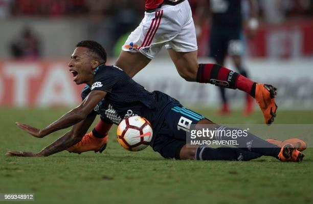 Ecuador's Emelec player Eduar Preciado falls after receiving a foul during the Copa Libertadores 2018 football match between Brazil's Flamengo and...