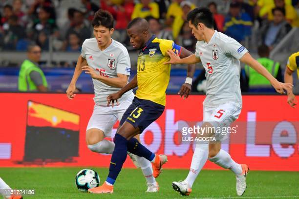 Ecuador's Enner Valencia is marked by Japan's Takehiro Tomiyasu and Naomichi Ueda during their Copa America football tournament group match at the...
