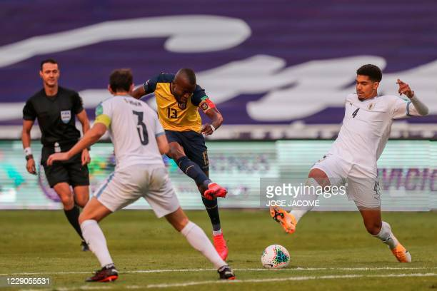 Ecuador's Enner Valencia vies for the ball with Uruguay's Diego Godin and Uruguay's Ronald Araujo during their 2022 FIFA World Cup South American...