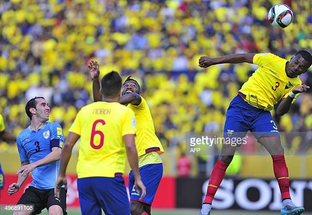 Ecuador's Frikson Erazo heads the ball next to teammates Cristian Noboa and Alexander Domingues and Uruguay's Diego Godin during their Russia 2018...