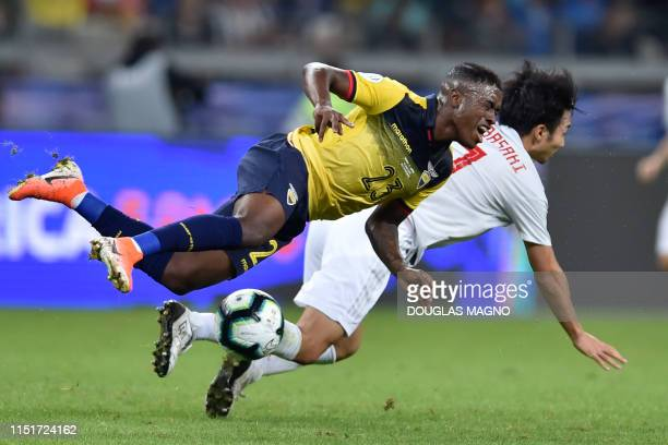 Ecuador's Jhegson Sebastian Mendez and Japan's Gaku Shibasaki fall during their Copa America football tournament group match at the Mineirao Stadium...