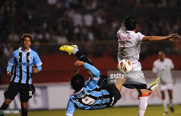 Ecuador's Liga de Quito Norberto Araujo vies for the ball against Brasil's Gremio Elano Blumer during their Copa Libertadores football match at the...