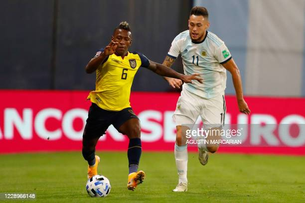 Ecuador's Pervis Estupinan is challenged by Argentina's Lucas Ocampos during their 2022 FIFA World Cup South American qualifier football match at La...
