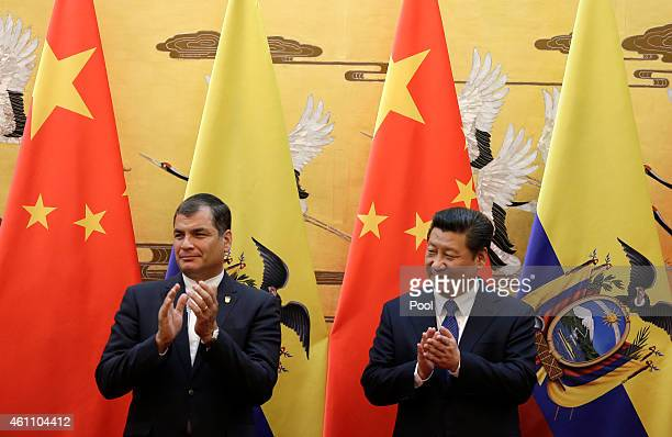 Ecuador's President Rafael Correa left and Chinese President Xi Jinping applaud after they witnessed a signing ceremony at the Great Hall of the...