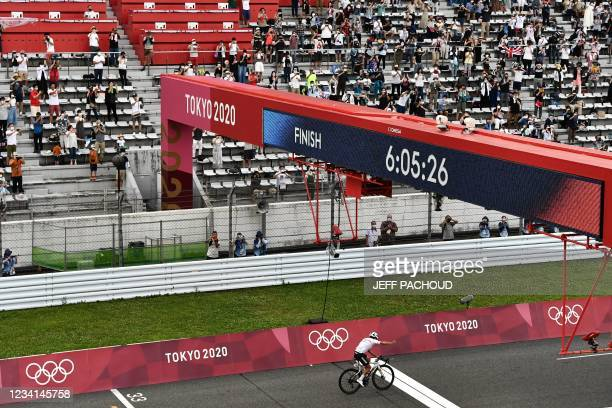 Ecuador's Richard Carapaz celebrates as he crosses the finish line to win the men's cycling road race during the Tokyo 2020 Olympic Games at the Fuji...