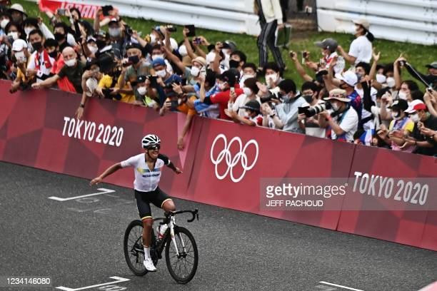 Ecuador's Richard Carapaz celebrates as he rides to the finish line to win the men's cycling road race during the Tokyo 2020 Olympic Games at the...