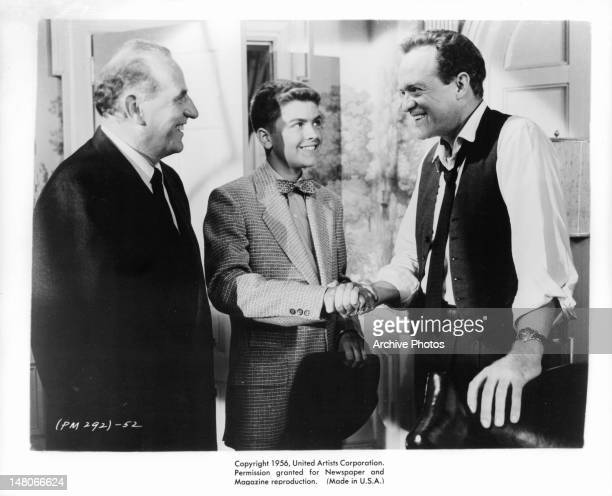 Ed Begley and Van Heflin smiling as Heflin shakes the hand of unidentified young man in a scene from the film 'Patterns' 1956